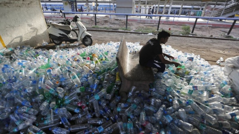 An Indian worker sorts used plastic bottles before sending them to be recycled at a railway station on World Environment Day in Ahmadabad, India, Tuesday, June 5, 2018. The U.N. says government bans on plastic can be effective in cutting back on waste but poor planning and follow-through have left many such bans ineffective. (AP Photo/Ajit Solanki)