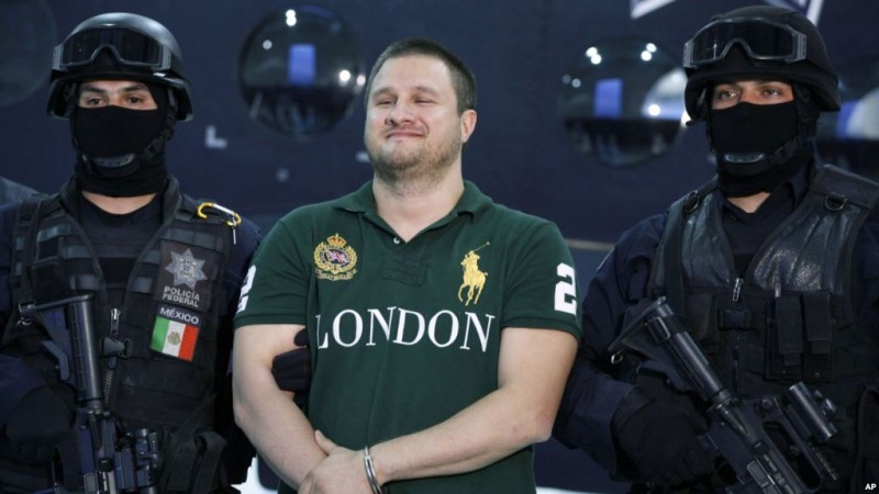 "HOLD FOR RELEASE WITH STORY BY MONDAY, JUNE 11, 2018 BY KATE BRUMBACK*** FILE -  In this Aug. 31, 2010 file photo, Texas-born fugitive Edgar Valdez Villarreal, alias ""the Barbie,"" center, smiles during his presentation to the press after his arrest in Mexico City. (AP Photo/Alexandre Meneghini, File)"