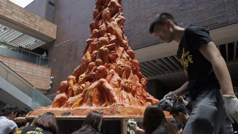 """University students clean the """"Pillar of Shame"""" statue at the University of Hong Kong, Monday, June 4, 2018. Tens of thousands of people are expected to attend an annual candlelight vigil for victims of the Chinese government's military crackdown nearly three decades ago on protesters in Beijing's Tiananmen Square. The statue with Chinese words that read """"June 4th massacre"""". (AP Photo/Kin Cheung)"""