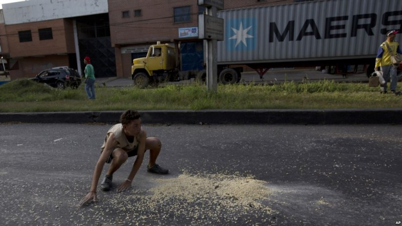 In this Jan. 23, 2018 photo, a youth moves quickly to collect grains of corn on the street that fell from a truck that was looted outside the port in Puerto Cabello, Venezuela. At the country's biggest port, people swarmed a corn-carrying truck and began filling up sacks with the grain while the driver was held at gunpoint. (AP Photo/Fernando Llano)