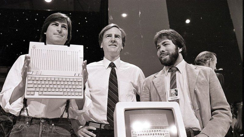 Apple. ARCHIVO - En esta foto de archivo del 24 de abril de 1984, Steve Jobs, presidente de Apple Computers, John Sculley, centro, presidente y CEO, y Steve Wozniak, cofundador de Apple, presentan la nueva computadora Apple IIc en San Francisco . Apple cumplió 40 años, y es una compañía muy diferente de la audaz startup que Jobs y Wozniak lanzaron en un garaje de Silicon Valley en 1976. (AP Photo / Sal Veder, Archivo).