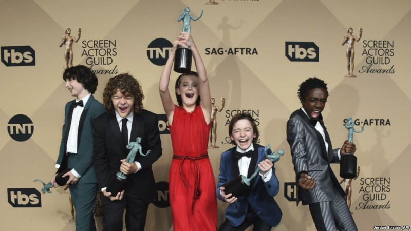 "De izquierda a derecha, Finn Wolfhard, Gaten Matarazzo, Millie Bobby Brown (de rojo), Noah Schnapp, y Caleb McLaughlin posan con el premio Screen Actors Guild a la excelencia en la actuación por ""Stranger Things"". Shrine Auditorium, Los Angeles, 29/1/17."